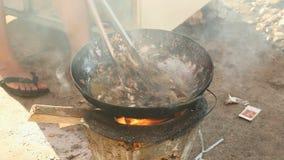 Het frituren van kikkers, houten brandend fornuis, gebraden kikkers stock videobeelden