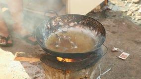 Het frituren van kikkers, houten brandend fornuis, gebraden kikkers stock video