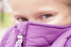 Het frozing het meisje van Nice verbergen achter het purpere vest stock afbeeldingen