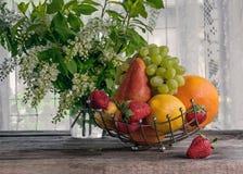 Het fruit, peer, grapefruit, citroen, perzik, aardbeien is in een mand op de achtergrond van een boeket van kleine witte bloemen  Royalty-vrije Stock Foto