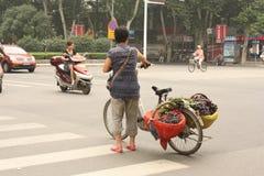 Het fruitverkoper van de straat met vruchten op haar fiets stock foto's
