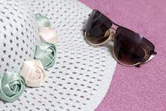 Het gaan op vakantie op het strand Hoed voor bescherming tegen de zon en een paar zonnebril Tegen de achtergrond van een strandha Royalty-vrije Stock Afbeelding