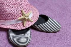 Het gaan op vakantie op het strand Hoed voor bescherming tegen de zon Strandtennisschoenen en Zeester Tegen de achtergrond van ee Royalty-vrije Stock Fotografie