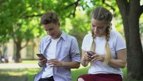 Het gadget wijdde vrienden gebruikend telefoons in park, gebrek aan mededeling, het negeren stock footage