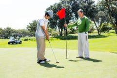 Het gatenvlag van de golfspelerholding voor vriend die bal zetten Royalty-vrije Stock Afbeeldingen