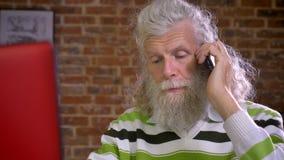 Het geïmpliceerde Kaukasische oude mannetje beantwoordt telefoongesprek terwijl het zitten op de Desktop en het typen op toetsenb stock videobeelden