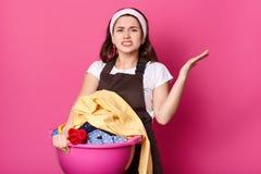 Het geïrriteerde boze huisvrouw stellen geïsoleerd over heldere roze achtergrond, die gebaar maken, die haar hand opzij met erger stock afbeelding