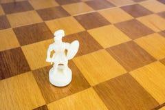 Het geïsoleerde witte schaakpand van steen op de vierkante houten raad Stock Foto