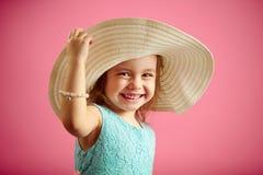 Het ge?soleerde portret van meisje in de hoed van Panama, glimlach, houdt handhoed, bevindt zich op roze ge?soleerde achtergrond stock foto's