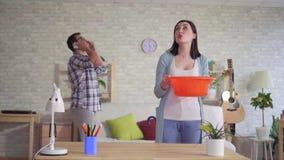 Het gealarmeerde jonge paar tijdens de vloedman die op de telefoon, vrouw spreken vangt een daling van water van het plafond stock footage