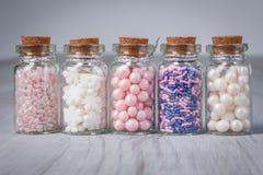 Het geassorteerde suikergoed bestrooit in miniglasfles stock afbeelding