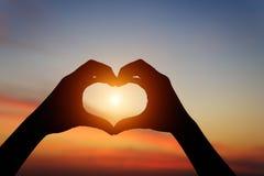Het gebaar die van de silhouethand liefde voelen tijdens zonsondergang royalty-vrije stock afbeelding