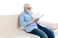 Het gebaarde die boek en de zitting van de mensenlezing op bank op wit wordt geïsoleerd Royalty-vrije Stock Afbeelding