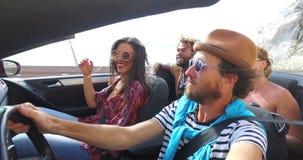 Het gebaarde hipstermens drijven in convertibel bij het winden van autosnelweg met vrienden stock footage
