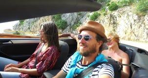 Het gebaarde hipstermens drijven in convertibel bij het winden van autosnelweg met vrienden stock video