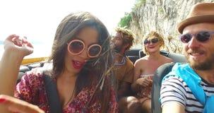 Het gebaarde hipstermens drijven in convertibel bij het winden van autosnelweg met vrienden stock videobeelden