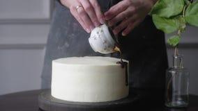 Het gebakjemeisje giet chocolade op een witte roomcake Langzame Motie