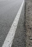 Het gebarsten asfalt op de weg, een ononderbroken strook en een deel van een kant van de weg royalty-vrije stock fotografie