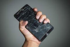 Het gebarsten smartphonescherm op handholding Stock Afbeeldingen