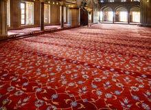 Het gebedgebied met rode tapijten in Sultan Ahmed Mosque wordt behandeld dat Stock Foto's