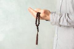 Het gebedparels van de mensengreep in handen royalty-vrije stock afbeeldingen