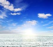 Het gebied van de sneeuw en blauwe bewolkte hemel Royalty-vrije Stock Afbeeldingen