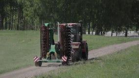 Het gebied van de tractorploeg dichtbij bos in de zomer stock footage
