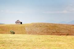 Het gebied van het gras, oud plattelandshuisje en blauwe hemel Stock Foto