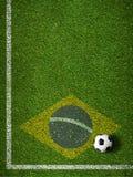 Het gebiedshoek van het voetbalgras met bal en vlag van Brazilië Stock Foto