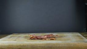 Het gebraden bacon, één plakworpen op een houten raad, vliegend bacon, zwarte isoleerde achtergrond stock videobeelden