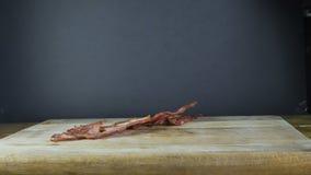 Het gebraden bacon wordt geworpen op een houten raad, vliegend bacon, zwarte geïsoleerde achtergrond stock footage