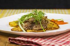 Het gebraden vlees met aardappels, wortelen en greens ligt op een plaat Royalty-vrije Stock Foto