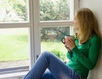Het gebroken hartmeisje zit op venstervensterbank drinkt koffie Royalty-vrije Stock Fotografie