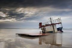 Het gebroken schip samen met het overzees op een zandige strand en een zonsondergang t stock foto