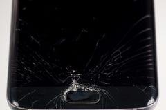 Het gebroken smartphonescherm, barsten en verbrijzeld glas onder diverse palingen stock foto