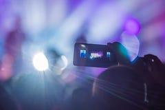 Het gebruik ging mobiele opname, pretoverleg vooruit en de mooie verlichting, Spontaan beeld van menigte bij rotsoverleg, sluit o royalty-vrije stock afbeelding