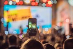 Het gebruik ging mobiele opname, pretoverleg vooruit en de mooie verlichting, Spontaan beeld van menigte bij rotsoverleg, sluit o stock afbeeldingen