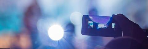 Het gebruik ging mobiele opname, pretoverleg vooruit en de mooie verlichting, Spontaan beeld van menigte bij rotsoverleg, sluit o stock afbeelding