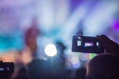 Het gebruik ging mobiele opname, pretoverleg vooruit en de mooie verlichting, Spontaan beeld van menigte bij rotsoverleg, sluit o stock fotografie