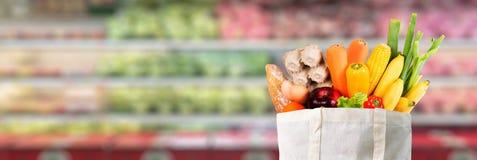 Het gebruik van de Ecodag het winkelen zak met groentenkruidenierswinkel die in sup winkelen Stock Foto's