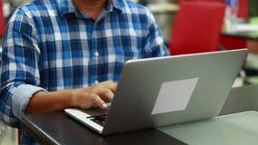 Het Gebruik van de mensenzitting het toetsenbord drukt het notitieboekje stock videobeelden