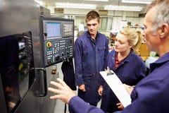 Het Gebruik van ingenieursteaching apprentices to automatiseerde Draaibank Royalty-vrije Stock Foto's