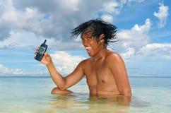 Het gebruiken van een cel-telefoon in een tropische overzees. stock afbeelding