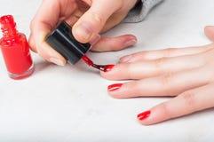 Het gebruiken van instrumentenborstel om rood poetsmiddel op vingernagel, zelfm toe te passen Royalty-vrije Stock Afbeeldingen