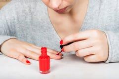 Het gebruiken van instrumentenborstel om rood poetsmiddel op vingernagel, zelfm toe te passen Stock Afbeeldingen