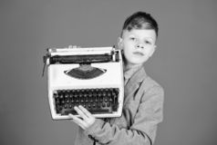 Het gebruiken van retro technologie Weinig jongen die retro schrijfmachine op blauwe achtergrond houden Kleine jongen die oude sc stock afbeelding