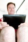Het gebruiken van Tablet op het Toilet Stock Afbeelding