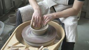 Het gebruiken van vochtige de vormenkom van de sponspottenbakker op het pottenbakkers` s wiel stock footage