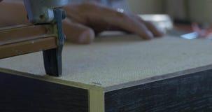 Het gebruiken van voornaamste kanon om achterkant van de kast in meubilairfabriek, close-up te bevestigen stock footage