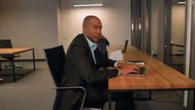 Het gebruiks bekijkt laptop van de portret ernstige Afrikaanse Amerikaanse jonge mens in bureau die en Internet werken surfen en  stock footage